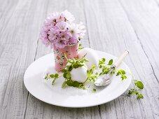 Teller mit Frühstückseiern, Salz und Blütensträusschen