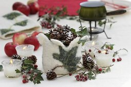 Wintry table decoration of candles, cones, crab apples & felt