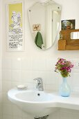 A vase of flowers on a wash basin and a mirror on a white-tiled wall