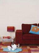 Eine rote Couch und blaues Tablett mit Teekanne und Tassen auf bunt kariertem Teppich