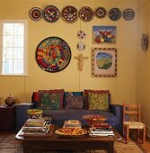 Blaue Couch mit bunten Zierkissen unter Tellersammlung