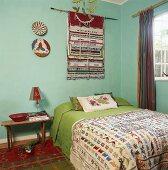 Doppelbett mit bunter Tagesdecke unter Wandteppich