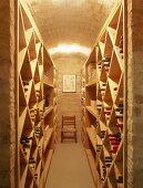 Rautenförmige Regale mit Weinflaschen im Weinkeller mit Tonnendecke