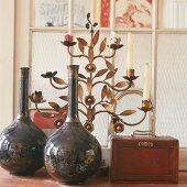 Porzellanvasen, Holzkästchen und floraler Kerzenständer aus Bronze vor einem Sprossenfenster