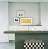Eine schlichte Küchentheke mit Granitplatte vor eine Schranknische mit Bilderrahmen
