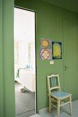 Ein antiker Stuhl unter Kinderzeichnungen an einer grünen Wand, daneben das Badezimmer