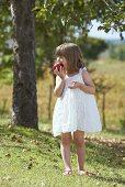 A little girl biting into an apple