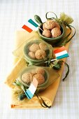 Amarettini in small bowls in satin bags with Italian paper flags as a present for guests