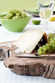 Parmesan cheese with grapes on a wooden board