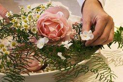 Making an arrangement of roses, coral fern & horned violets