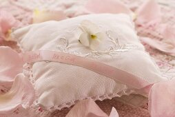 Rose-scented pillow with horned violet and pink ribbon