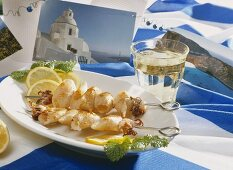 Squid kebabs, white wine and Greek table decoration