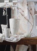 White vases and spring twigs in front of torn wallpaper