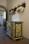 Chest of drawers painted with flowers cloakroom with hats in a entrance to a country home