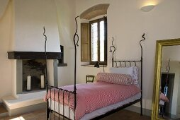 Iron bedstead with white pink bed linen in a Mediterranean country home