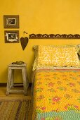 Bed with a printed bedspread and rustic stool in front of a yellow wall