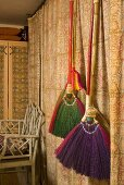 Colorful brooms hanging in front of a curtain