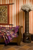 Decorative wooden column and antique sofa in front of wallpaper with an orange and white striped pattern