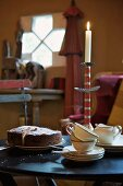 Coffee and cake on a table with a burning candle in a candle holder