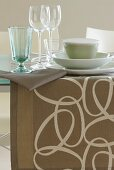 A dining table with a table runner and glasses