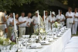 Wedding table in white, wedding guests in the background