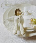 A white place setting with an embroidered serviette and a flower