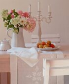A bunch of flowers in a jug, a candle holder and a plate of fruit