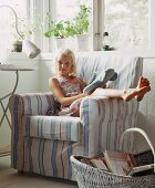 A blonde girl sitting in an armchair