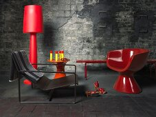 Red floor lamps and a bowl chair on a dark flagstone floor in front of a weathered, grey stone wall