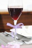 Mit rotem Getränk gefülltes Glas und einer Schleife dekoriert