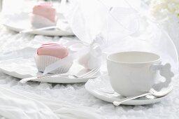 Feierlich dekoriertes Dessert und weisses Kaffeegeschirr