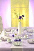 An elegantly laid Easter table with a purple flower in a vase
