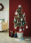 A small Christmas tree decorated with crocheted snowflakes