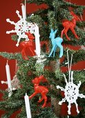 A small Christmas tree decorated with crocheted snowflakes and plastic deer