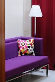 A view of a purple sofa with a colourful cushion and a floor lamp behind