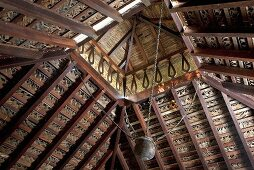 An Indian wooden ceiling with an offset roof and a hanging metal pot