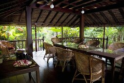 A covered terrace with wicker furniture and ball lights in a tropical surroundings