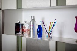 Flagons, bottles and a glass of coloured sticks on a shelf above a built-in cupboard