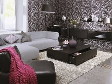 A grey sofa, a leather armchair and a black coffee table in a the corner of a living room with a brown and white papered wall