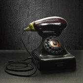 An old-fashioned telephone with an aubergine as the receiver