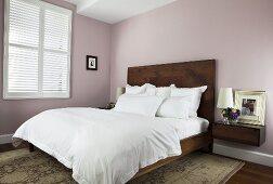 Schlafraum mit Doppelbett, hochgezogenem Kopfteil in Holzausführung & Nachtkonsole vor pastellrosa gefärbter Wand