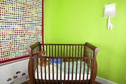 Gitterbettchen aus Holz in Kinderzimmerecke vor grüner Wand & gepunktetem Raffrollo