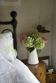 Flowers in a white pitcher on a bedside table