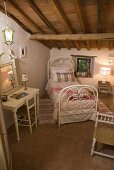 White, antique iron bed with a dressing table and mirror under a rustic timber frame ceiling