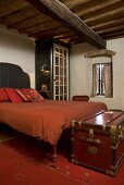 Red leather hope chest in front of a bed with red bed linen under a timber frame ceiling
