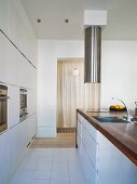 White designer kitchen - kitchen area with wooden countertop and stainless steel faucet with vent
