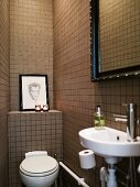 Toilet and sink in a narrow bathroom with brown tiles