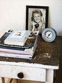 Side table with framed photo and magazines