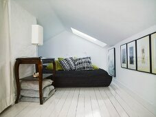 Antique side table with table lamp in a cozy bedroom under a ceiling with a skylight