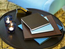 Folders and tea lights on a dark side table